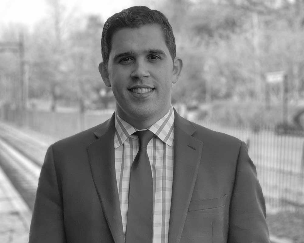 Black and white photo of Jason Perez wearing a suit jacket and tie