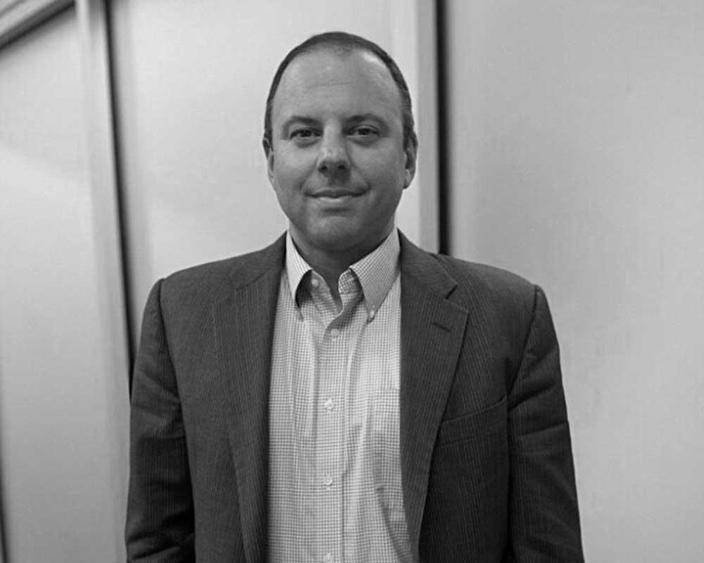 Black and white profile photo of Jason Spiro wearing blazer and collared shirt