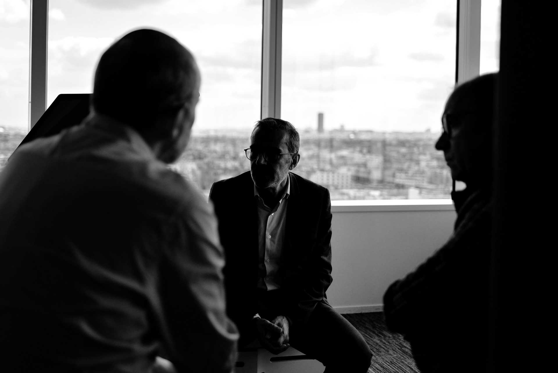 Three business men sitting together in an office with a few of a city skyline